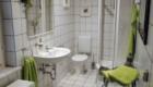 Gefliestes Bad mit Dusche, Waschbecken, Toilette und Fenster