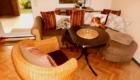 Wohnzimmer mit Sofa, Couchtish und Korbsessel